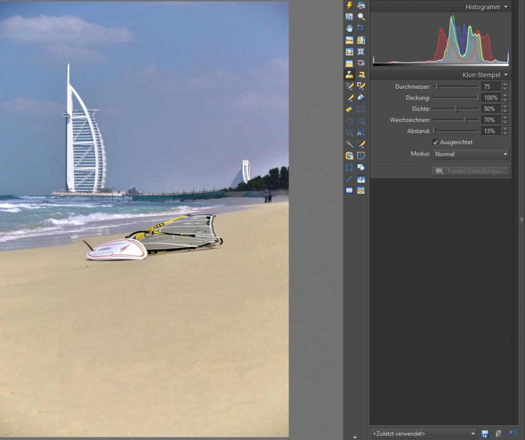 Stellen Sie zuerst die Darstellung des Fotos auf der Arbeitsfläche auf Originalgröße (Symbol 1:1) ein. Danach suchen Sie einen geeigneten Durchmesser des Klon-Stempels aus und durch Mausklick bei gleichzeitigen Halten der Strg-Taste nehmen Sie den Quellbereich auf. So können Sie schrittweise den Strand retuschieren.