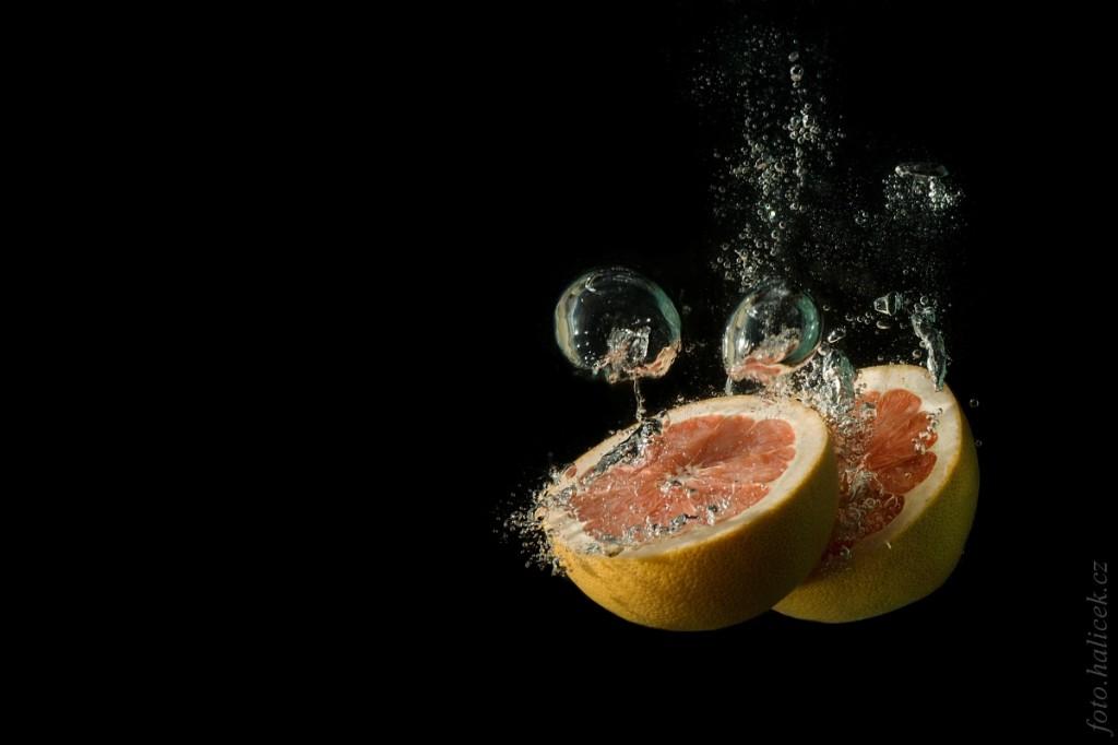 Grapefruithälften. Canon 1000D, EF 75-300 mm bei 80 mm, 1/200 s, f/9.0, ISO 100. Bei der Aufnahme wurde im Nachhinein der Hintergrund ausgebessert und abgedunkelt.