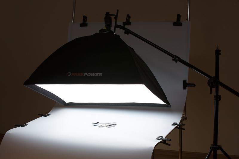 Eine im Vergleich zu den kleinen Produkten relativ große Softbox erzeugt eine sich unter vielen verschiedenen Winkeln spiegelnde Lichtquelle. In dieser Szene wurde ein Fototisch benutzt, genauso gut hätte es aber auch mit einer Tischdecke als Unterlage funktioniert.