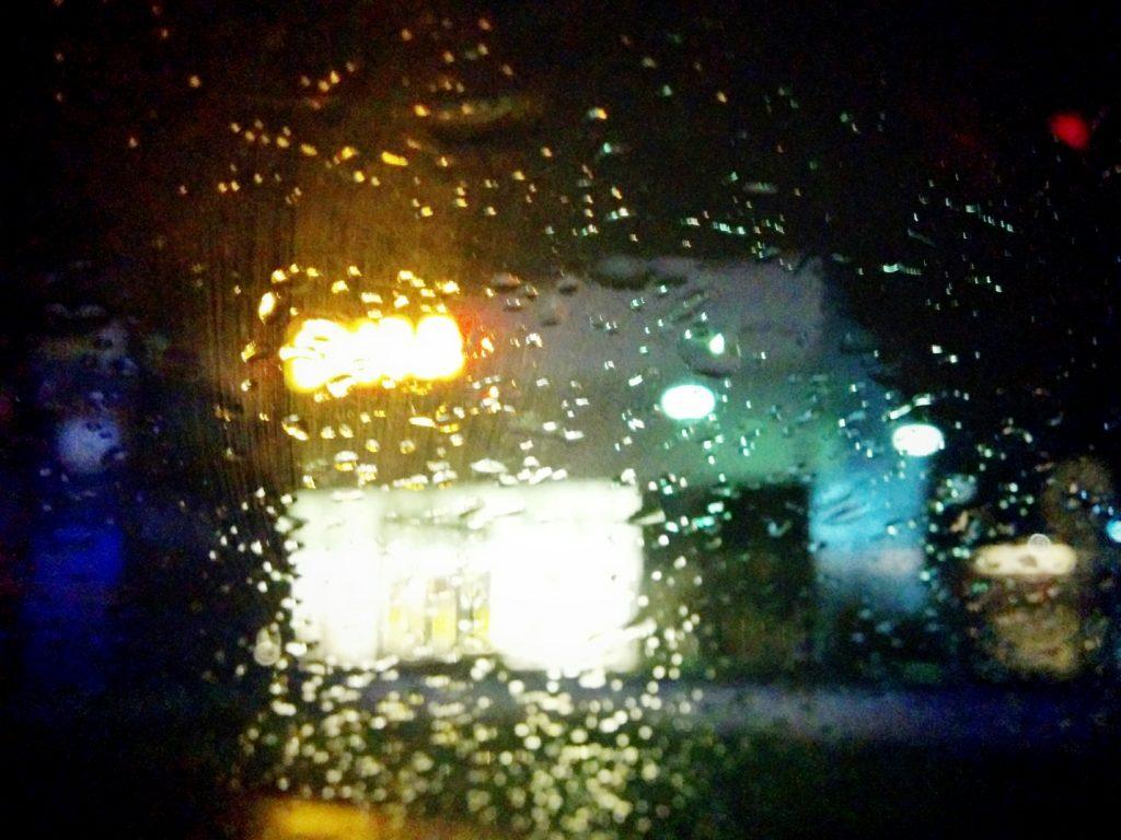Frontscheibe im Regen vor einem Einkaufcenter.