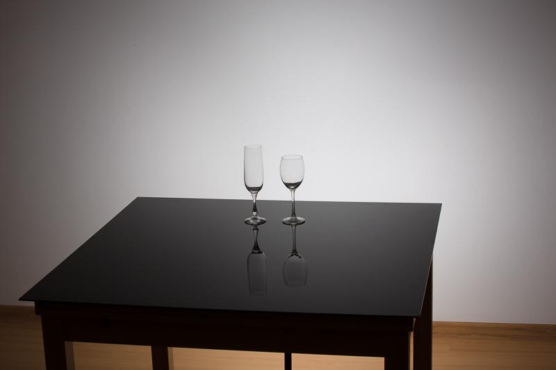 Szenenaufstellung. Unter dem Tisch ist das einzige verwendete Licht versteckt, welches die Wand beleuchtet.