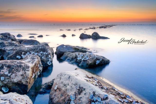 Die Steine füllen den ganzen Vordergrund aus und führen bis zum Hintergrund, der das Meer und den Himmel trennt.