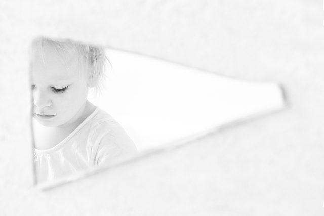 Das Gesicht des Kindes ist in der Scherbe des Spiegels eingerahmt.