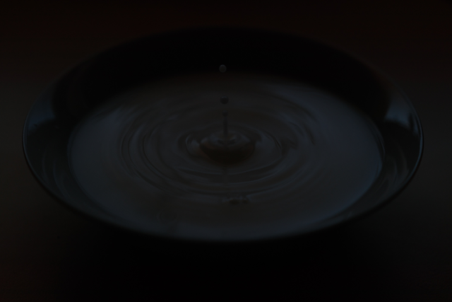 Ein Tropfen, der auf die Oberfläche fällt. Auf diesem Bild wollte ich die Bewegung des Tropfens mithilfe einer kurzen Verschlusszeit einfrieren. Aufgrund unzureichendem Lichts ist das Bild unterbelichtet, obwohl ich eine niedrige Blende verwendet habe.