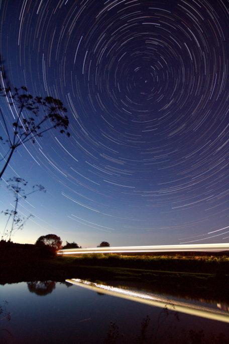 5 Tipps, wie man Startrails fotografiert: Sterne und Zug.