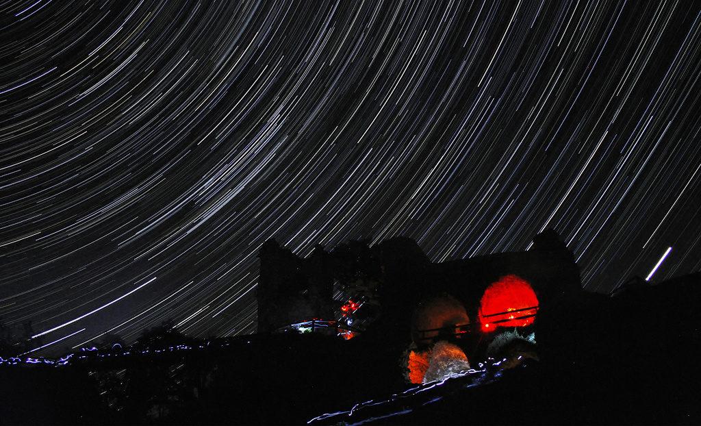 Beherrschen Sie das Fotografieren der Sternspuren. 5 Tipps, wie man Startrails fotografiert: Sternspuren über der Bergruine Zubštejn.