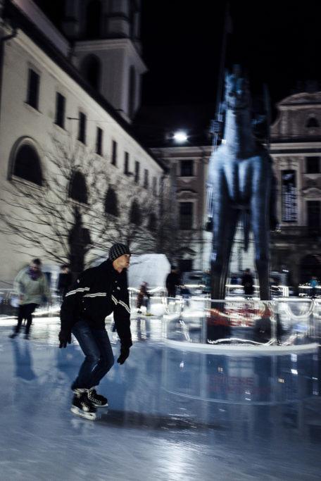 Während der Hintergrund verschwommen ist, wird der Eiskunstläufer relativ scharf abgebildet.