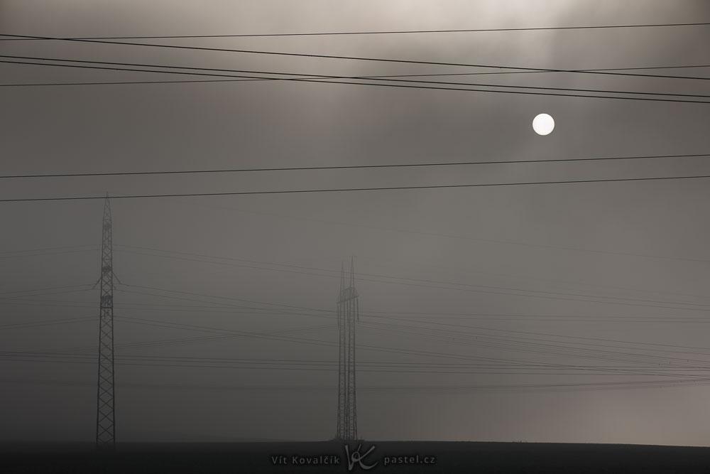 Landschaftsaufnahmen mit dem Teleobjektiv: Oberleitungsmasten im Nebel mit Sonnenlicht am Nachmittag.