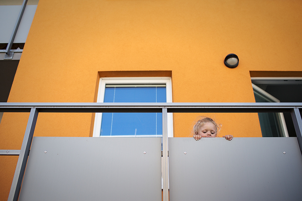 Die kräftige Farbe der Fassade bildet den Hintergrund für das Porträt des kleinen Mädchens.