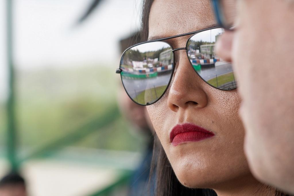 Sportfotografie: Grundlegende Tipps, wie man Sportevents fotografiert : Die Spiegelung in der Sonnenbrille habe ich dazu genutzt, um einen Teil der Rennbahn von der Zuschauerbühne zu erfassen.
