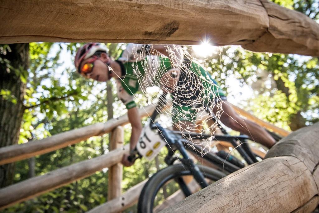 Grundlegende Tipps, wie man Sportevents fotografiert: Das ungewollte Nachfokussieren auf das Spinnennetz vor dem Rennradfahrer hat mich zu dieser Komposition inspiriert.