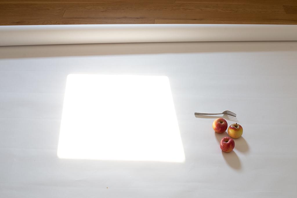 """Stillleben fotografieren: Auf diesem Foto sieht man die """"Hintergrundkulisse"""" für das künftige Bild mit dem Apfel und der Gabel."""